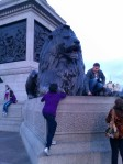 Sophia climbing to pose with the lion at Trafalgar Square